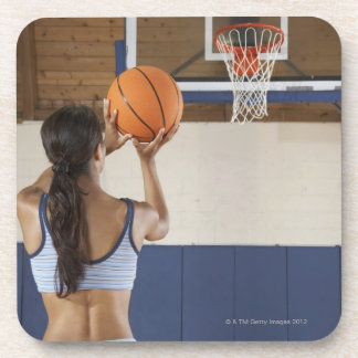 Woman aiming at hoop with basketball, rear view drink coaster