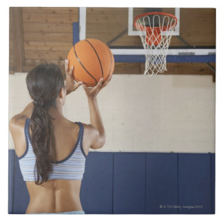 Woman aiming at hoop with basketball, rear view tile
