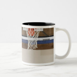 Woman aiming at hoop with basketball, rear view Two-Tone coffee mug