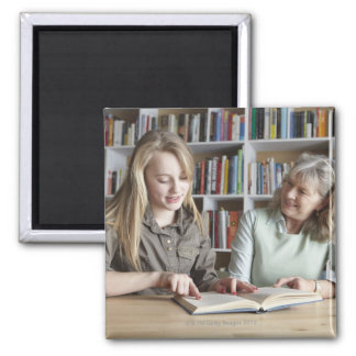 Woman and granddaughter reading together magnet