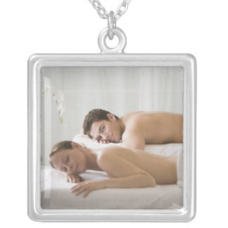 woman and man lying on massage benches silver plated necklace