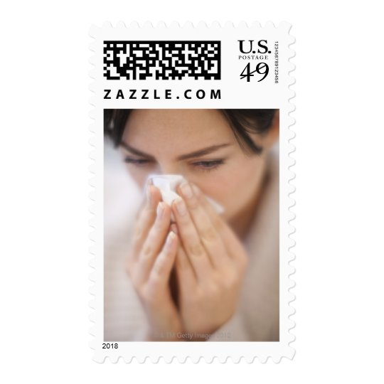 Woman blowing her nose. postage