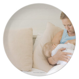 Woman breastfeeding baby dinner plate