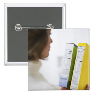 Woman comparing nutrition labels 2 inch square button