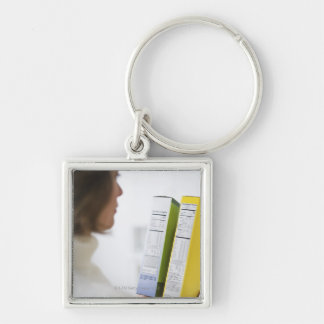 Woman comparing nutrition labels Silver-Colored square keychain