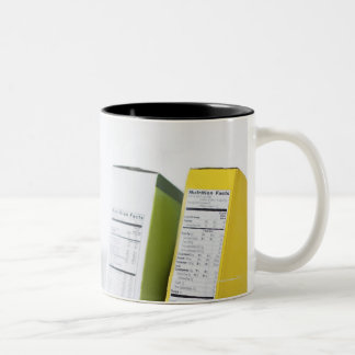 Woman comparing nutrition labels Two-Tone coffee mug