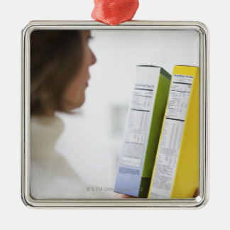 Woman comparing nutrition labels square metal christmas ornament