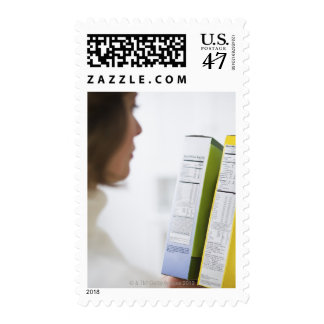 Woman comparing nutrition labels postage