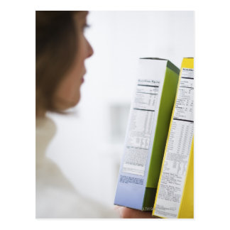 Woman comparing nutrition labels postcard
