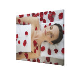Woman covered in flower petals laying on massage canvas print