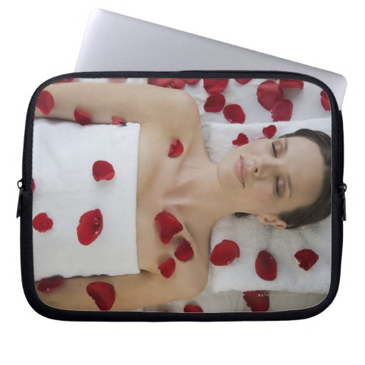 Woman covered in flower petals laying on massage laptop computer sleeves