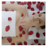 Woman covered in flower petals laying on massage large square tile