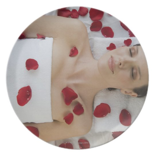 Woman covered in flower petals laying on massage melamine plate