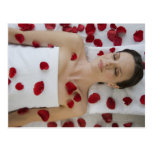 Woman covered in flower petals laying on massage postcard