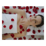 Woman covered in flower petals laying on massage poster