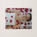 Woman covered in flower petals laying on massage jigsaw puzzles