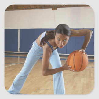Woman crouching with basketball, portrait square sticker