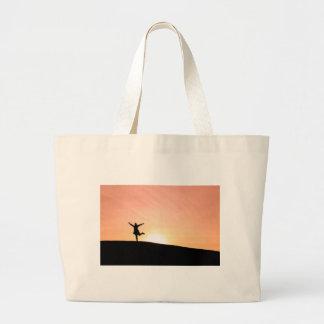 Woman dancing against the setting sun large tote bag
