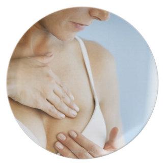 Woman doing breast self exam 2 dinner plate