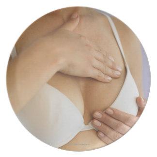 Woman doing breast self exam dinner plate