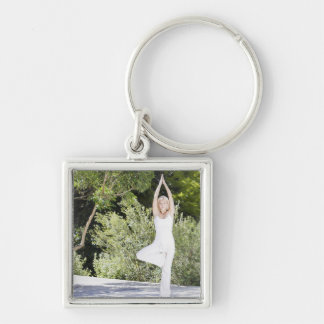 Woman doing yoga on patio Silver-Colored square keychain