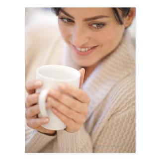 Woman drinking a hot drink. postcard