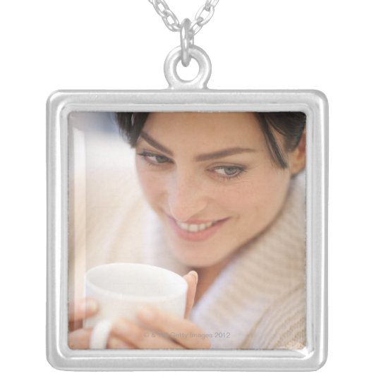 Woman drinking a hot drink. silver plated necklace