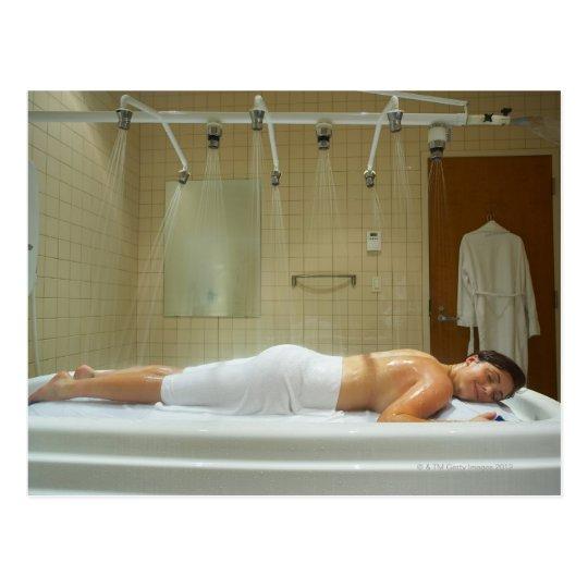 Woman enjoying hydrotherapy in vichy shower postcard