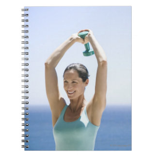 woman excercising with weights on her roof notebooks