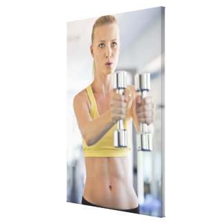 Woman exercising with weights stretched canvas print
