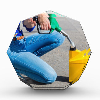 Woman filling yellow can with gasoline or petrol. award