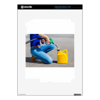 Woman filling yellow can with gasoline or petrol. decal for iPad 2