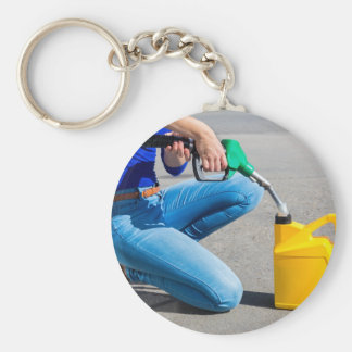 Woman filling yellow can with gasoline or petrol. keychain