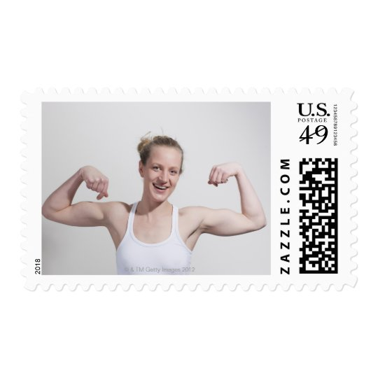 Woman flexing muscles postage