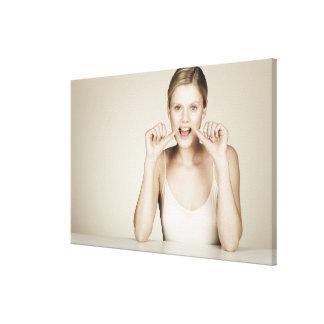 Woman flossing her teeth canvas print