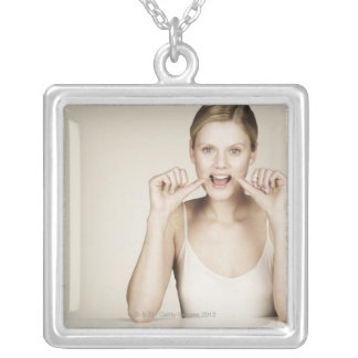 Woman flossing her teeth silver plated necklace