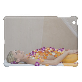 Woman getting a flower treatment at a spa. iPad mini covers