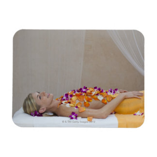 Woman getting a flower treatment at a spa. magnet