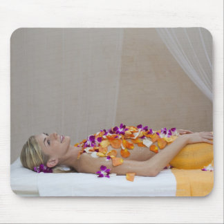 Woman getting a flower treatment at a spa. mouse pad