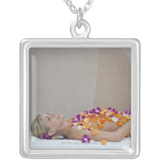 Woman getting a flower treatment at a spa. silver plated necklace