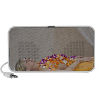 Woman getting a flower treatment at a spa. travelling speaker