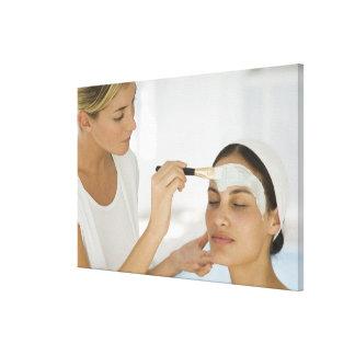 Woman getting beauty mud mask canvas print