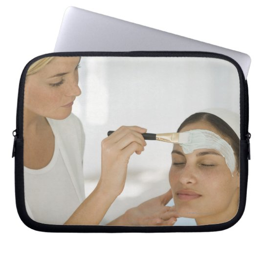 Woman getting beauty mud mask laptop sleeve