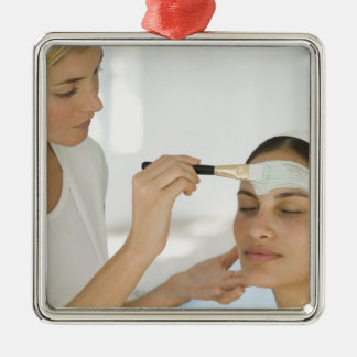 Woman getting beauty mud mask metal ornament