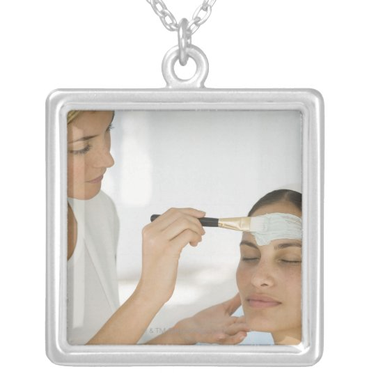 Woman getting beauty mud mask silver plated necklace