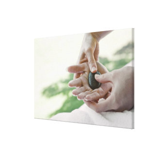 Woman getting hand massage with hot stone stretched canvas prints