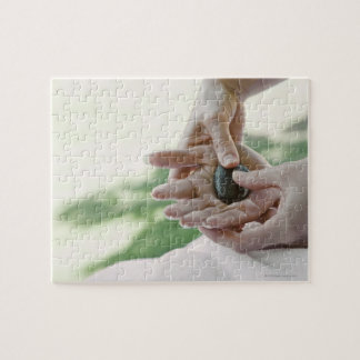 Woman getting hand massage with hot stone jigsaw puzzle