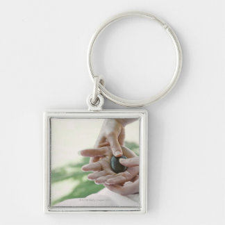 Woman getting hand massage with hot stone keychain