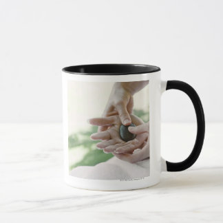 Woman getting hand massage with hot stone mug