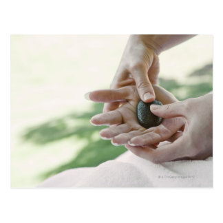 Woman getting hand massage with hot stone postcard